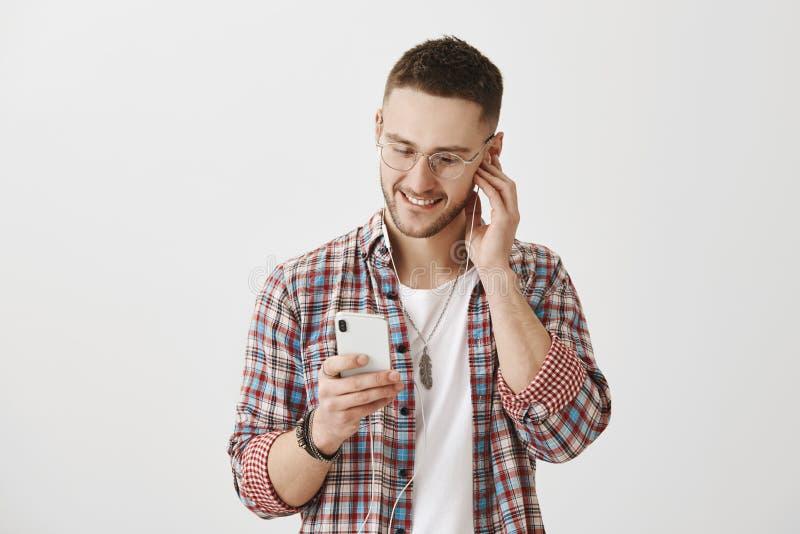 Musik beschreibt Gefühle Atelieraufnahme des attraktiven kaukasischen Kerls in den Gläsern, die den Schirm von Smartphone, wählen lizenzfreie stockfotografie