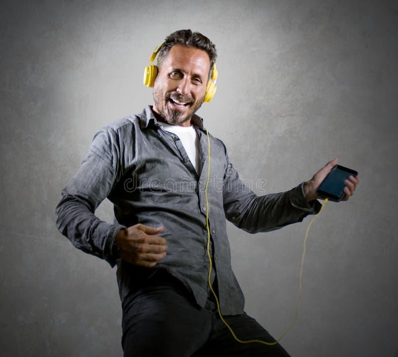 musik för lycklig och upphetsad attraktiv man för 40-tal lyssnande online-med hörlurar och mobiltelefonen som sjunger sång och at arkivfoto
