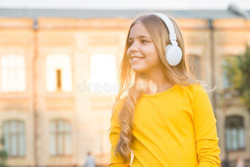Musik för själ Modernt barn Musikkanal Flickor som lyssnar på musik i modern gadget Kid lycklig med trådlöst headset royaltyfria foton