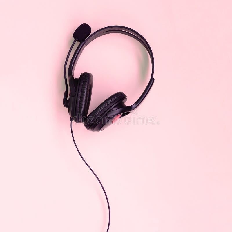 Musik-h?rendes Konzept Schwarze Kopfh?rerl?gen auf rosa Hintergrund stockfotografie
