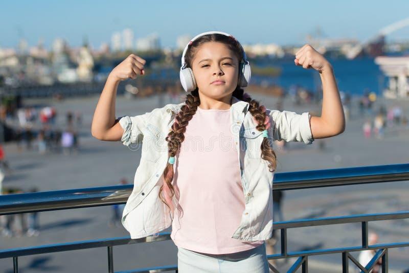 Musik har att läka makt Det förtjusande barnet tycker om musik som spelar i hörlurar på stads- bakgrund r royaltyfria foton