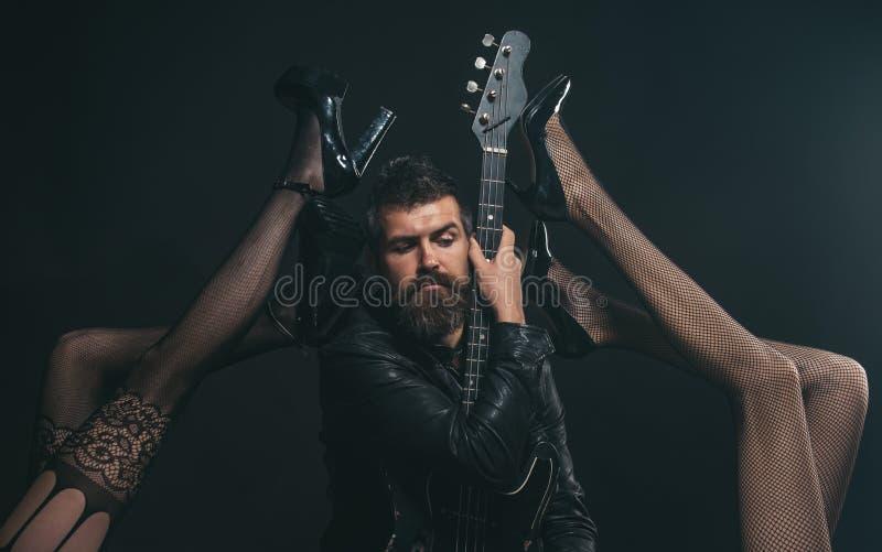Musik ist seine Leidenschaft Bärtiger Mann mit der Gitarre gereizt durch sexy Beine in der Fetischwäsche Fühlen flirty Wie Rockst stockfotografie