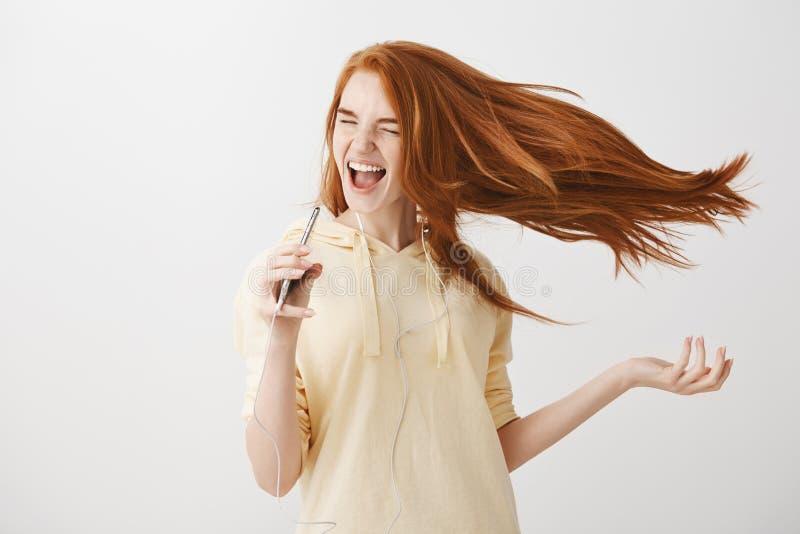 Musik lädt Vertrauen und Glück auf Porträt der emotionalen hübscher Frau mit rotem Haartanzen und Gesanglied stockbild