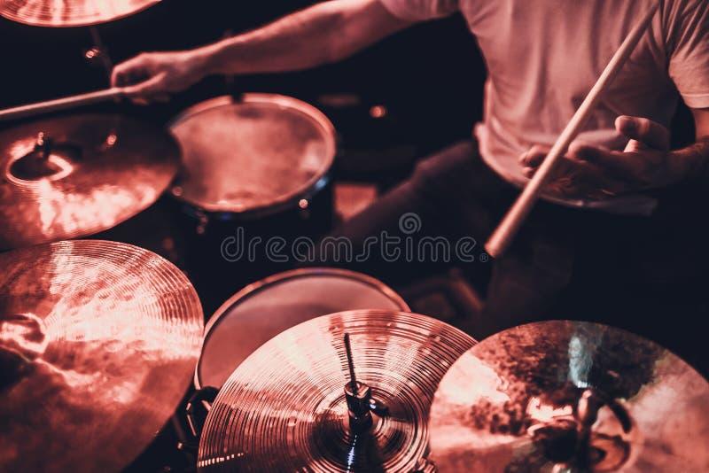Musik, Menschen, Musikinstrumente und Unterhaltungskonzept - männlicher Musiker oder Schlagzeuger spielt Drum-Kit im Studio über  stockfoto