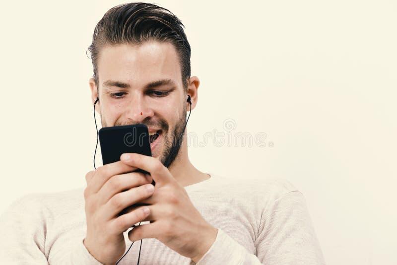 Musik- och grejbegreppsgrabben med skägget rymmer spelaren MP3 och bär hörlurar arkivfoton