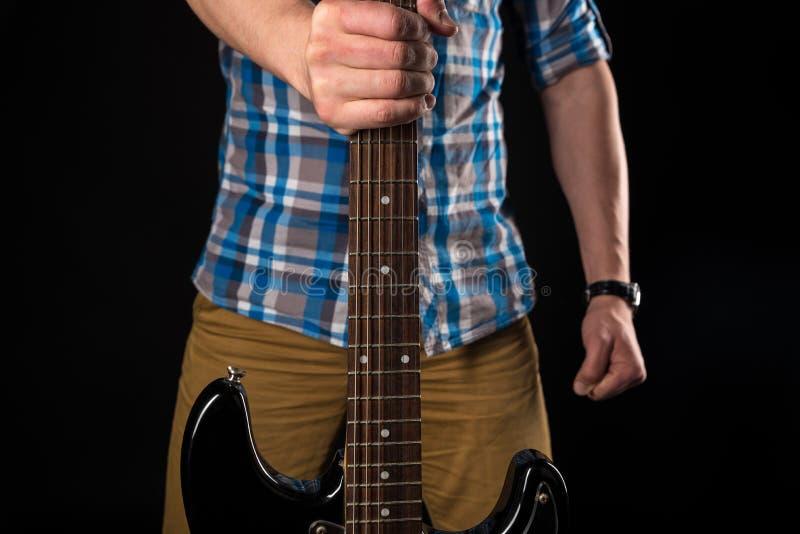 Musik och konst Gitarristen rymmer en elektrisk gitarr i hans assistent, på en svart isolerad bakgrund leka för gitarr horizonta royaltyfri foto