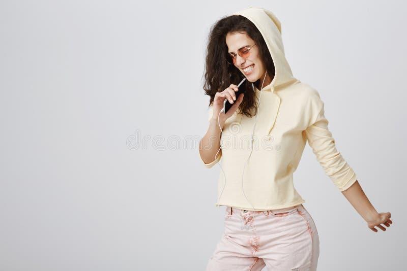 Musik- och livsstilbegrepp Glad snygg stads- flicka med lockigt hår som bär den moderiktiga dräkten och den stilfulla eyewearen royaltyfri bild