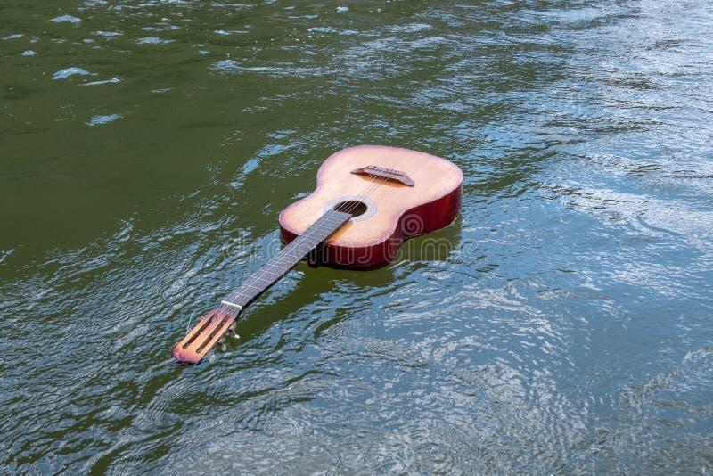 Musik sjunker inte En akustisk gitarr svävar i en flod, sjön eller annan kropp av vatten Begreppet av skeppsbrott, flod, tragedi arkivbild