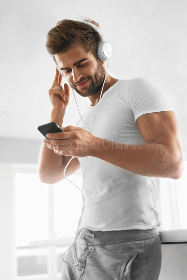 Musik som lyssnar Man i hörlurar genom att använda mobiltelefonen inomhus arkivfoton