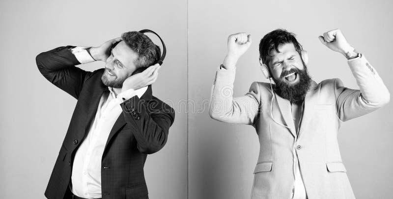 Musik und entspannt sich Genießen bärtiger Gesichtsgesellschaftsanzug der Männer Lied Titelliste für Büroarbeit Musikbruch währen lizenzfreie stockfotos