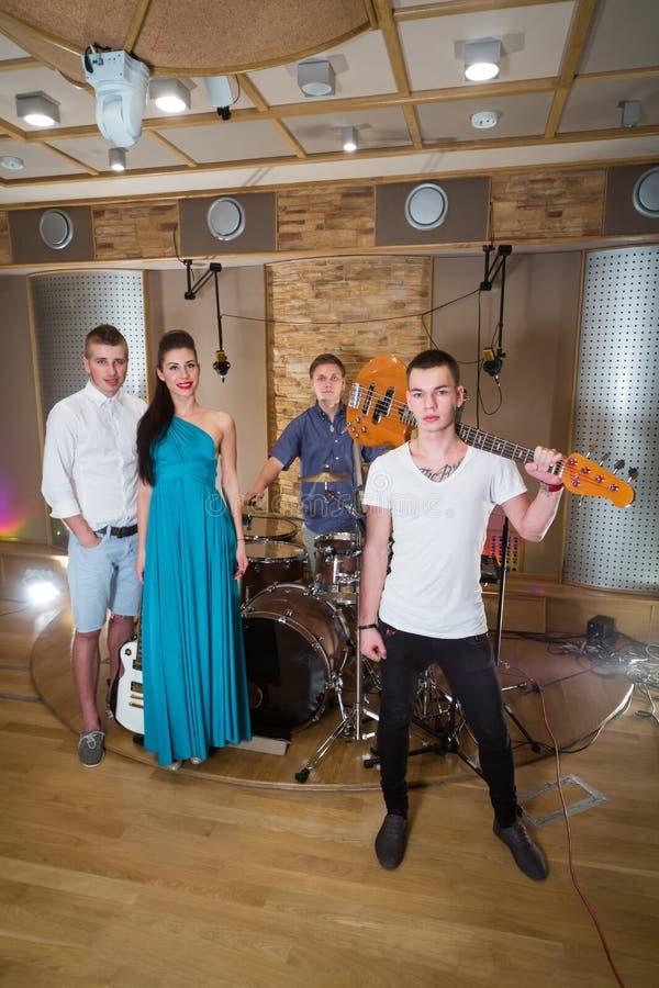 Musikalische Gruppe von drei Kerlen und von einem Mädchen im Tonstudio stockfotografie