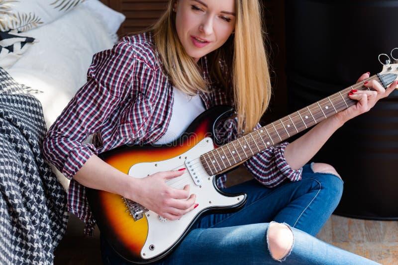 Musikalische Talenthobbyfrau, die den Gitarren-Gesang spielt stockfotografie