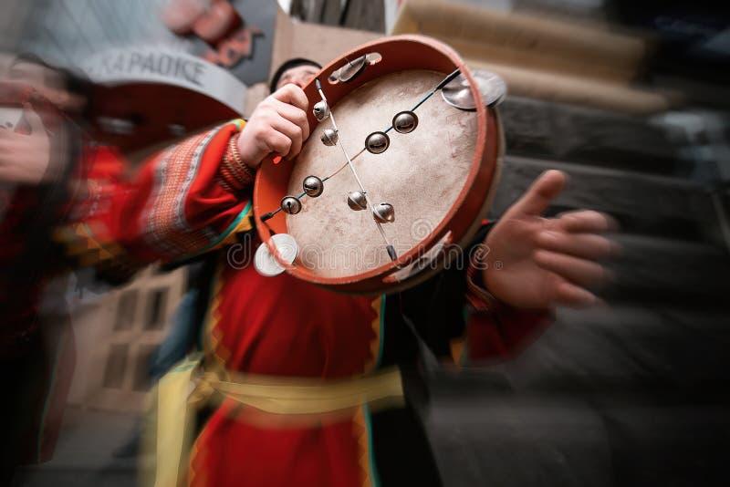 Musikalisk tamburin i händerna av en iklädd folk för man arkivbilder