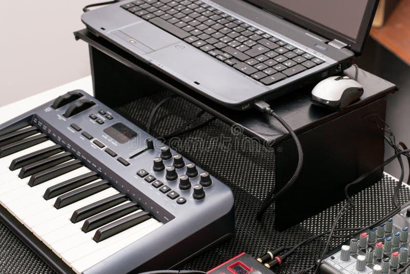 Musikalisk utrustning - bärbar dator och ett mini- piano arkivbilder