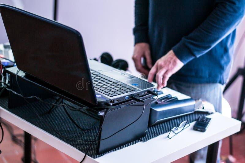 Musikalisk utrustning - bärbar dator och ett mini- piano - musiker som spelar pianot arkivbilder