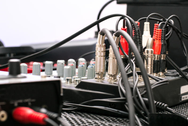 Musikalisk utrustning - som är nära upp av kablar och knappar - svart som är röd, silver royaltyfria foton