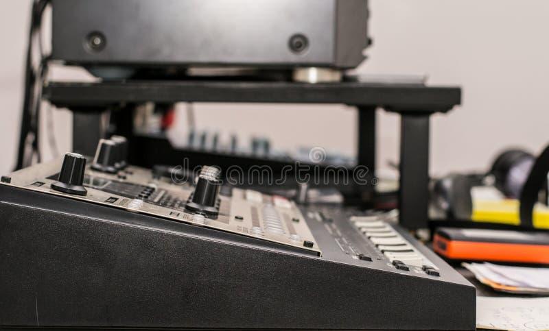 Musikalisk utrustning - som är nära upp av piano och förstärkaren royaltyfri bild