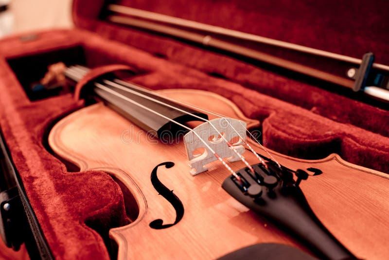 musikaliska instrument Slut upp fiolen och pilbåge i öppet mörkt - rött fall royaltyfri foto