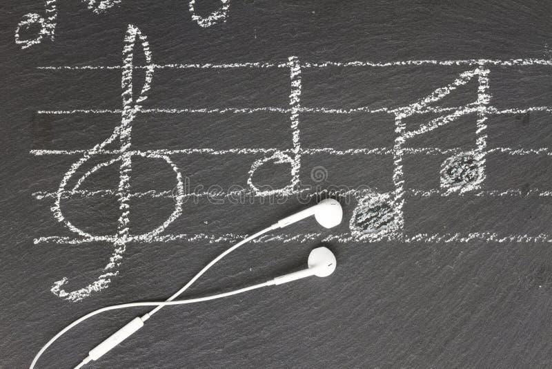 Musikanmärkningar med hörlurar royaltyfri foto