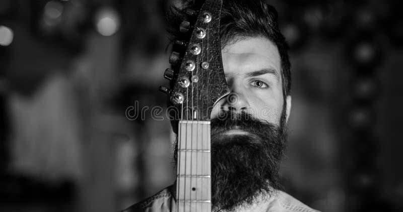Musikanmerkung im Inneren Musiker, Künstler auf nachdenklichem, ruhigem Gesicht und Gitarrenhals lizenzfreie stockfotografie