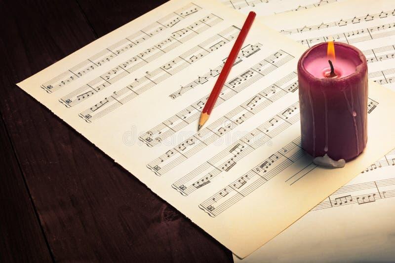 Musikanmerkung und -brennende Kerze lizenzfreies stockfoto