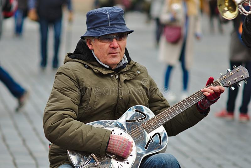 Musikant playing guitar at Old Town Square stock photography