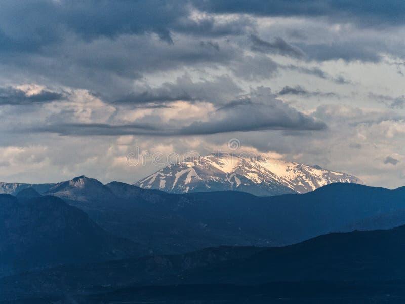 Musikband av solljus på snö mellan mörka moln och berglutningar royaltyfri fotografi