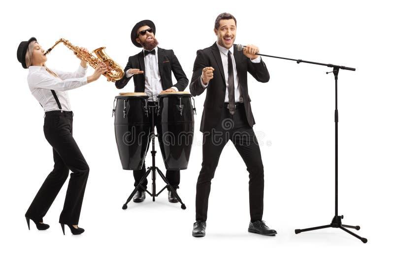 Musikband som spelar på en saxofon och congavalsar, och en sångare som sjunger på en mikrofon royaltyfri bild