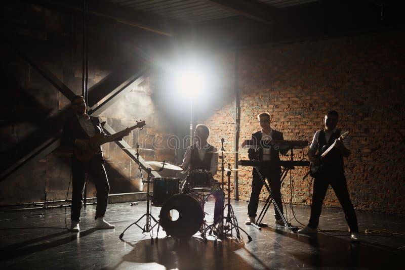 Musikband und -mode Hübsche junge Männer in den Klagen, die Rock spielen und Lied singen Bandschattenbilder mit an einem Konzert stockbild