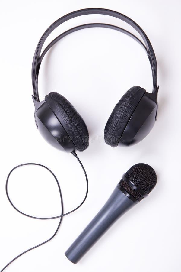 Musikbegrepp - mikrofon och hörlurar över vit royaltyfria foton