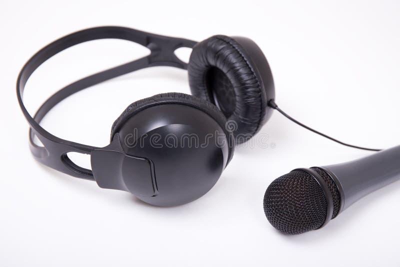 Musikbegrepp - som är nära upp av mikrofonen och hörlurar över vit royaltyfria foton