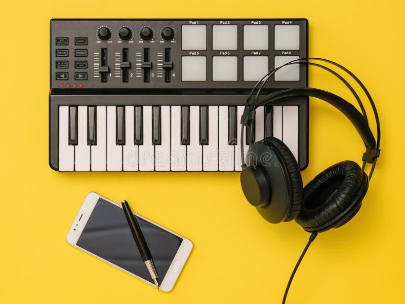 Musikblandare, smartphone, hörlurar och penna på gul bakgrund Begreppet av arbetsplatsorganisationen royaltyfri foto