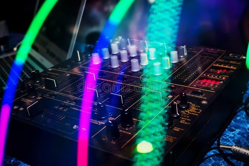 Musikblandaren med knoppar och volym jämnar för den yrkesmässiga discjockeyn som blandar i nattklubb royaltyfri foto