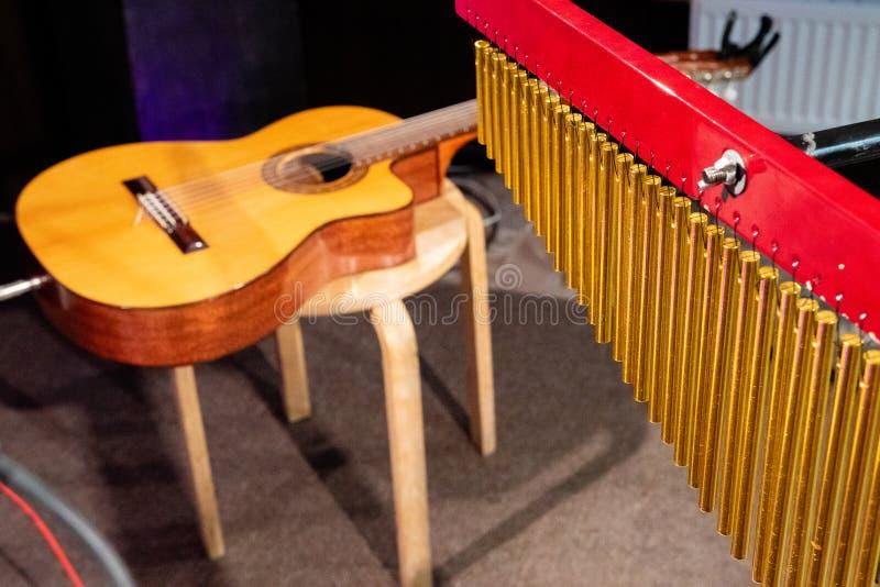 Musiken av vinden från rören i förgrunden, i bakgrunden den akustiska gitarren arkivfoto