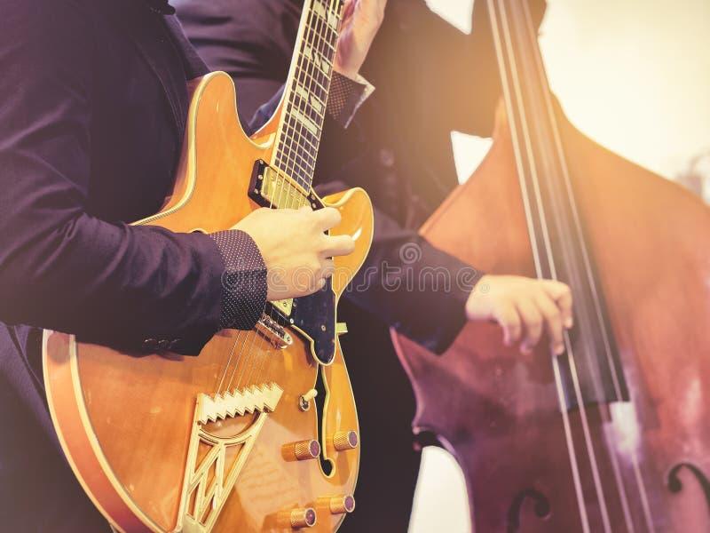 Musiker, der Gitarre elektrisches klassisches Konzert mit Cello spielt lizenzfreie stockfotos