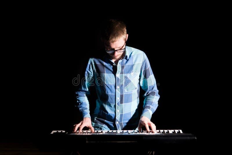 Musiker, der Tastatur mit Musikinstrument auf dunklem Hintergrund spielt Musikerkonzept stockbilder