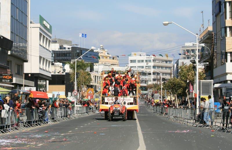 Musiker i karnevaldräkter som fortskrider en gata i en flöte arkivfoto