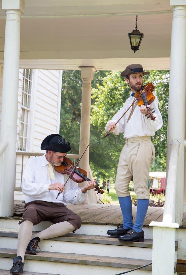 Musiker i koloniala dräkter arkivbild