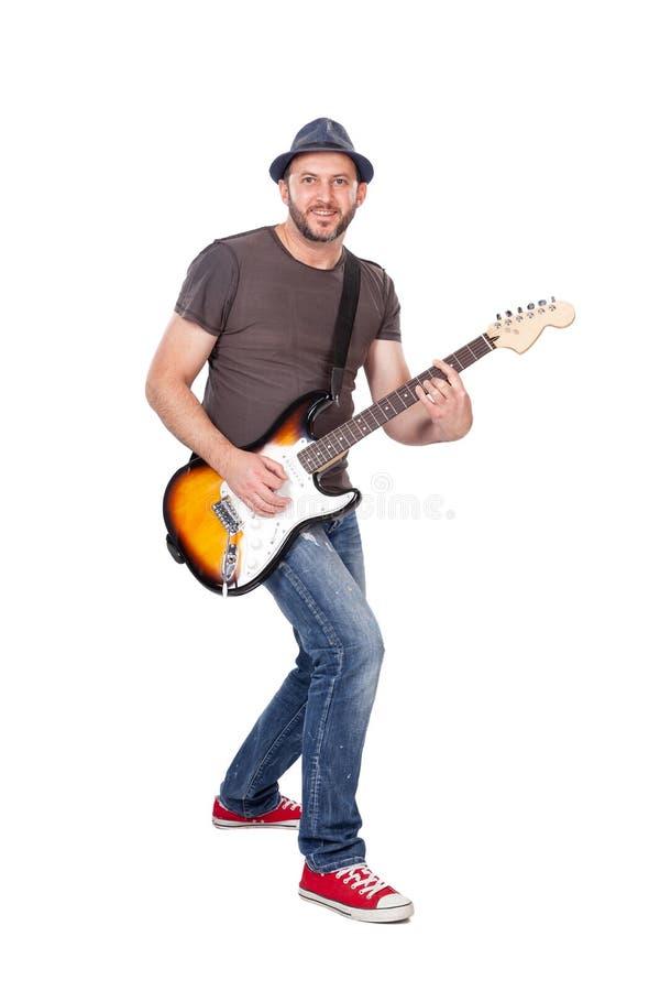 Musiker ler, leker elgitarr med entusiasm Isolerade på vitt fotografering för bildbyråer