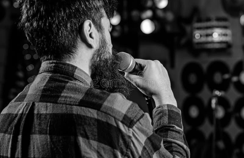 Musiker mit Bart-Gesanglied im Karaoke, hintere Ansicht Rocksängerkonzept Kerl mag in der dunklen Karaokehalle singen Mann lizenzfreies stockbild