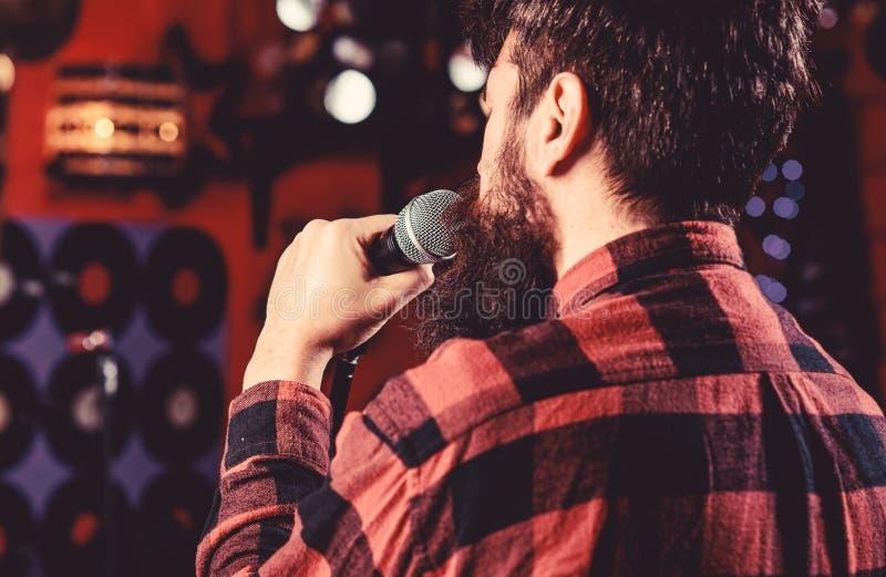 Musiker mit Bart-Gesanglied im Karaoke, hintere Ansicht Rocksängerkonzept Kerl mag in der dunklen Karaokehalle singen Mann lizenzfreies stockfoto