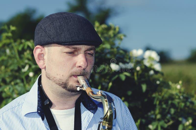 Musiker-Saxophone Roses Field-Kappen-Holzblasinstrument-Instrument-Leistungs-Natur-Haltung Jazz Blues stockfoto