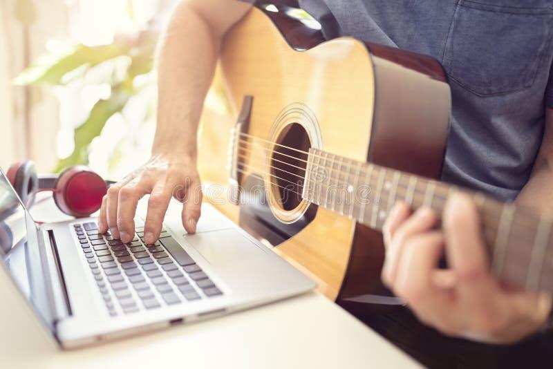 Musiker som spelar den akustiska gitarren och antecknar musik på datoren royaltyfria foton