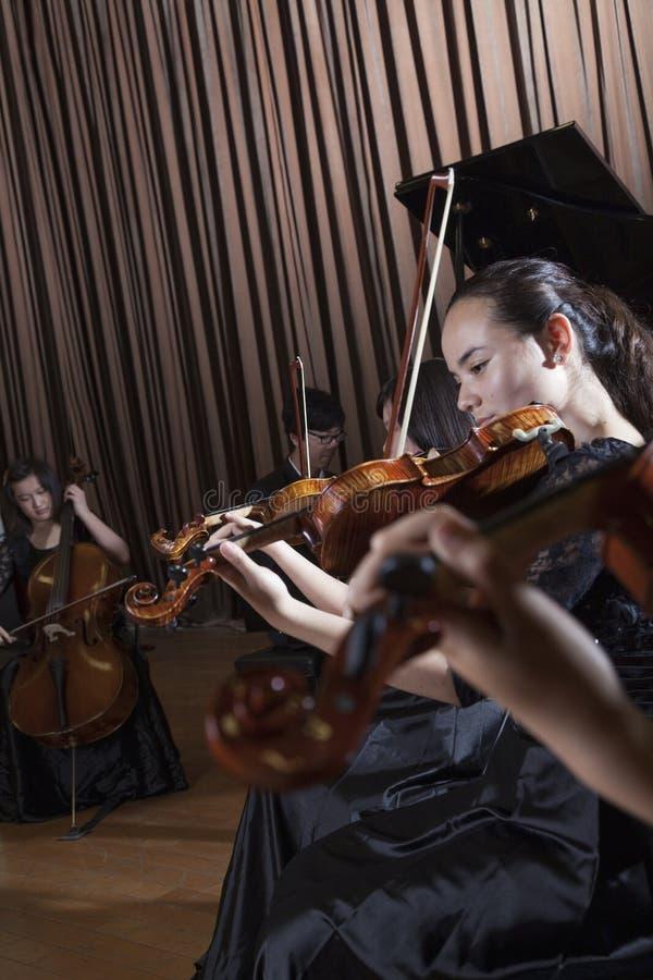 Musiker som spelar under en kapacitet, violinister på framdelen royaltyfri foto