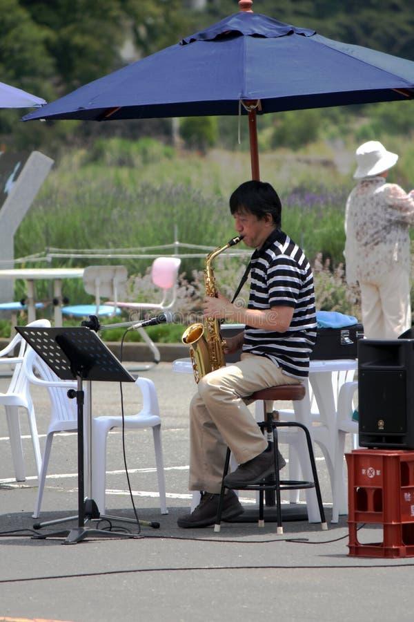 Musikern att spela saxofonen i trädgården för att ge nöjeunderhållning för folket royaltyfri fotografi