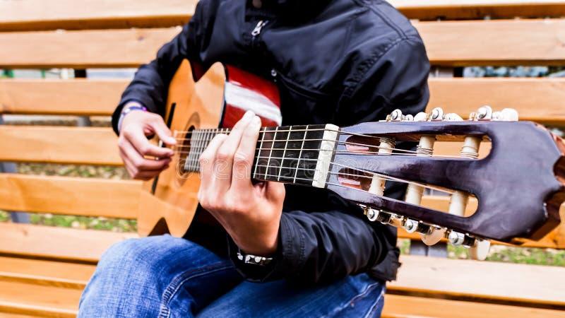 Musikern som spelar gitarren parkerar offentligt royaltyfri foto