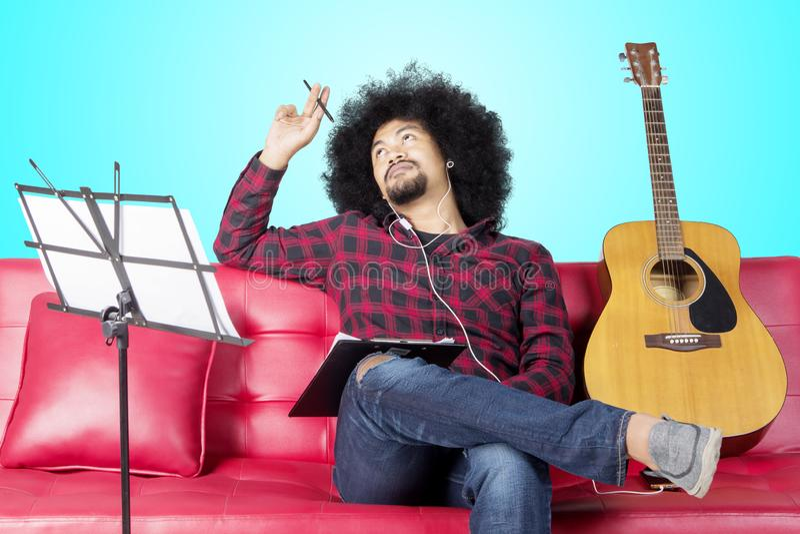Musikern tänker för komponerar sång på studio royaltyfria bilder
