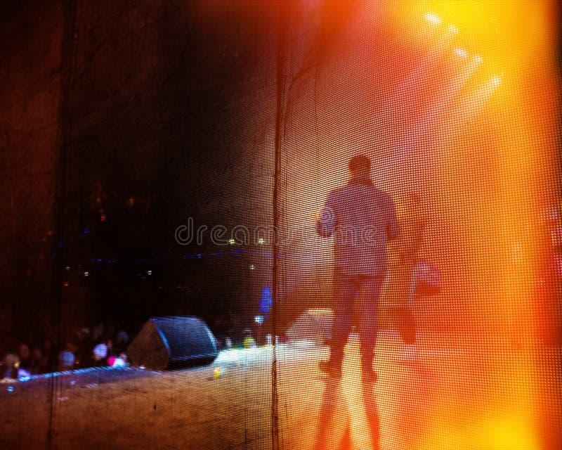 Musikern utför en rockbandkonsert i aftonen i den öppna luften och fansen arkivbild