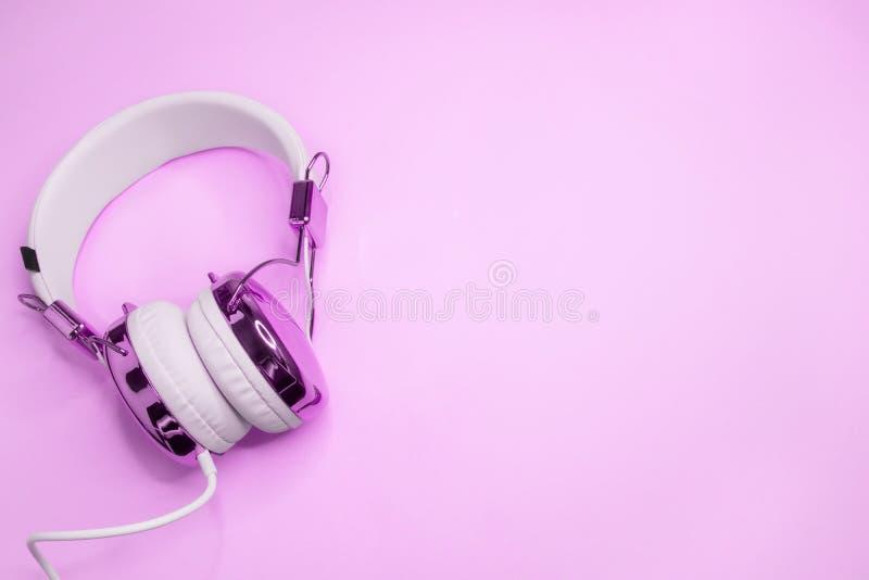 Musikhintergrund mit purpurroten Kopfh?rern stockbilder