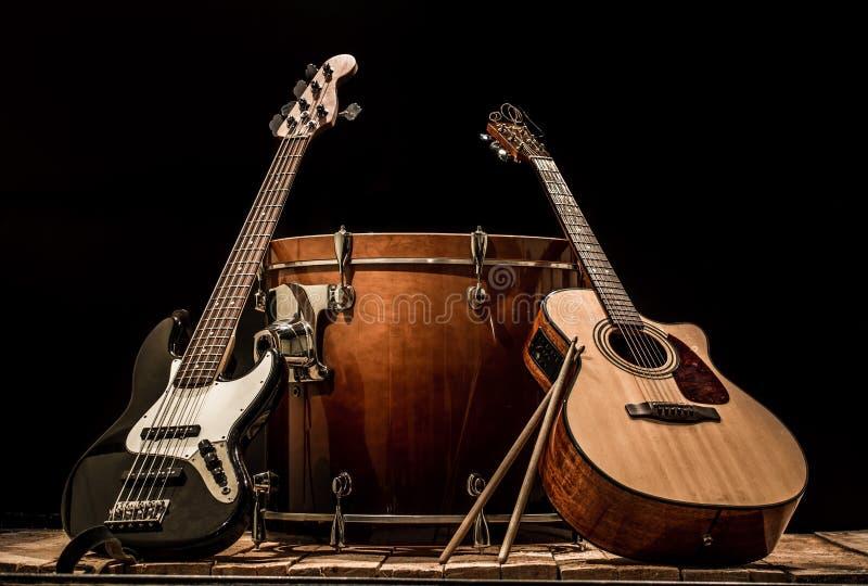 musikinstrument, akustisk gitarr för bastrummatrumma och elbas på en svart bakgrund arkivbild